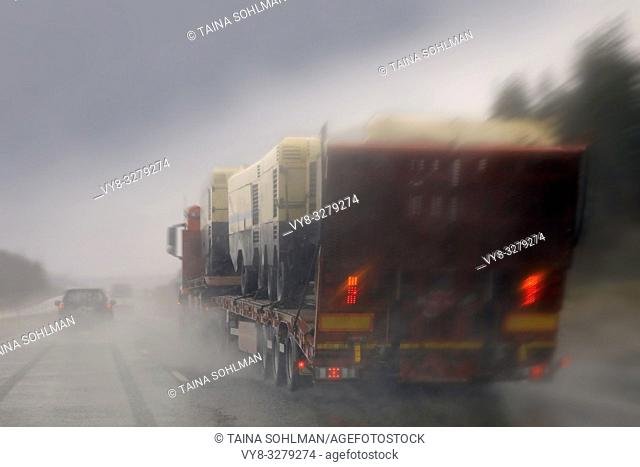 Driving along highway in rain and passing a semi truck with a load of machinery, rainwater splashing, blurred view
