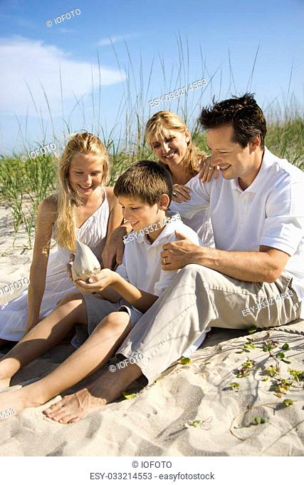 Caucasian family of four sitting on beach looking at seashell