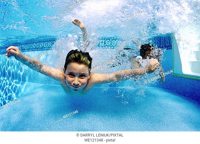 Underwater photograph of two boys, aged 5 and 7 years old, jumping into swimming pool