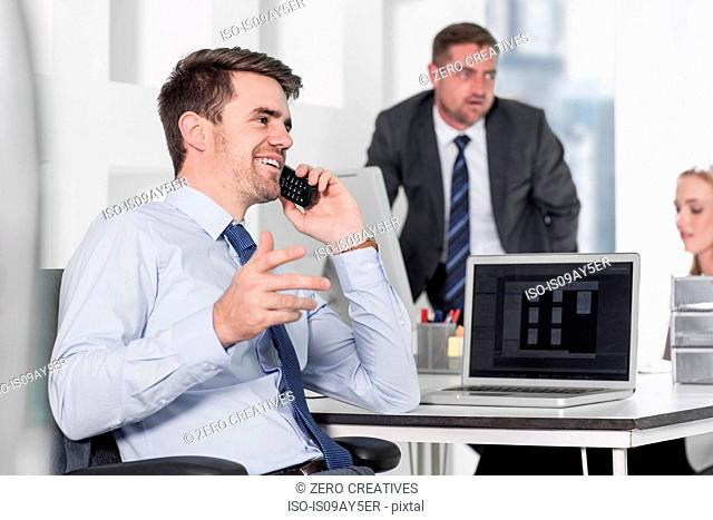 Businessman and businesswoman working, colleague on phone in office