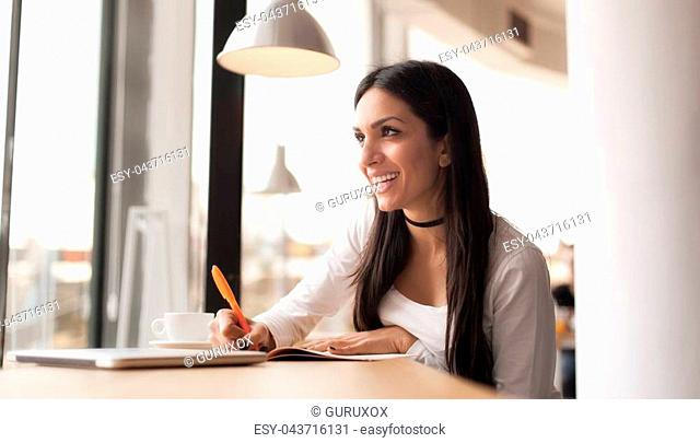 Attractive young woman writing in her notebook and drinking coffee in street cafe