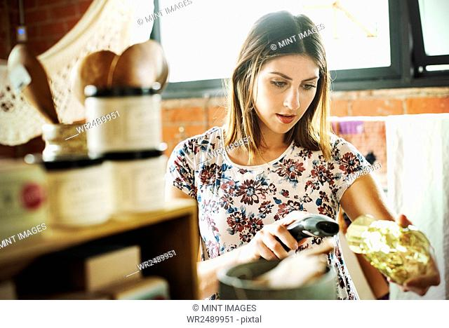 Young woman in a shop, scanning the barcode of a drinking glass with a barcode scanner