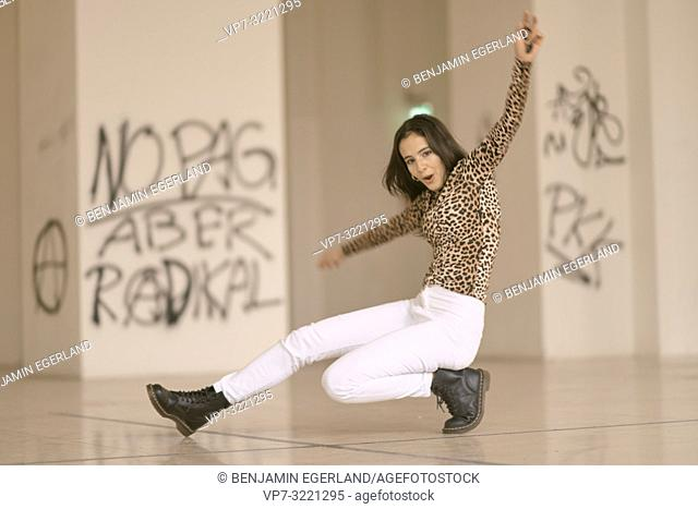 portrait of playful vibrant woman dancing on floor, wearing fashionable leopard print sweater, in Munich, Germany