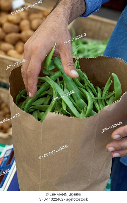 Green beans in a paper bag at a market