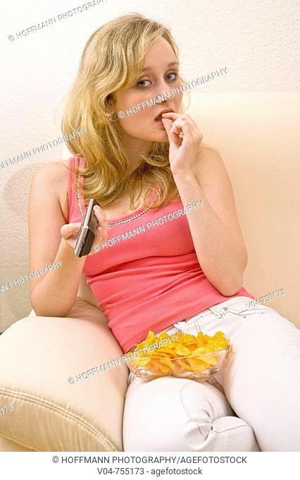 Young woman zapping and eating chips