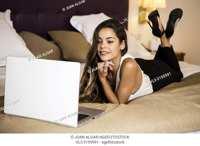 Charming young lady in casual outfit smiling and using modern laptop while lying on soft bed in luxury hotel room