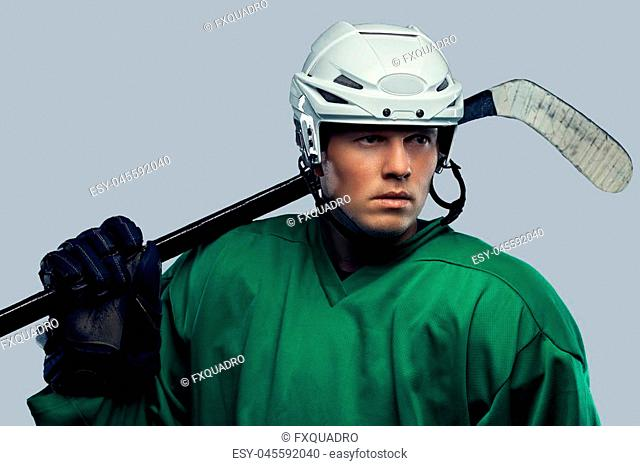 Professional hockey player in full equipment with gaming stick on shoulders. Isolated on a gray background