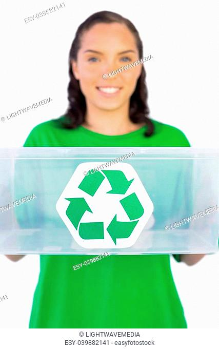 Smiling woman giving a recycling box to the camera against white background