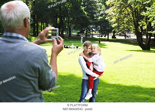 Woman senior man and girl taking photographs in the park Sweden