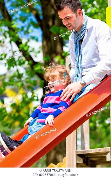 Vater und Tochter auf Rutsche auf Spielplatz