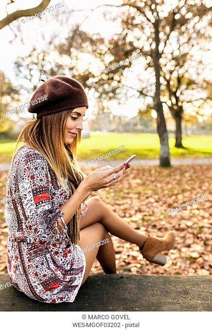 Smiling young woman sitting on bench in autumnal park looking at cell phone