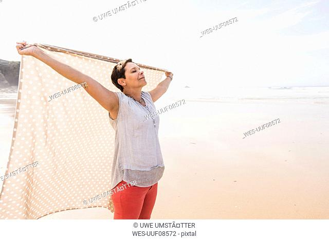Mature woman on the beach lifting a blanket