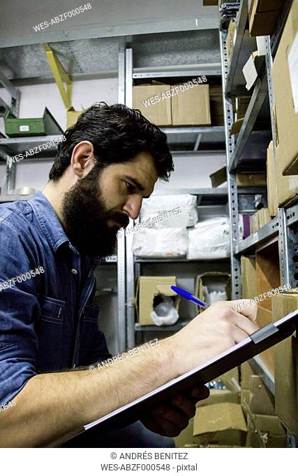 Manan examining business inventory, writing on a clipboard in a warehouse