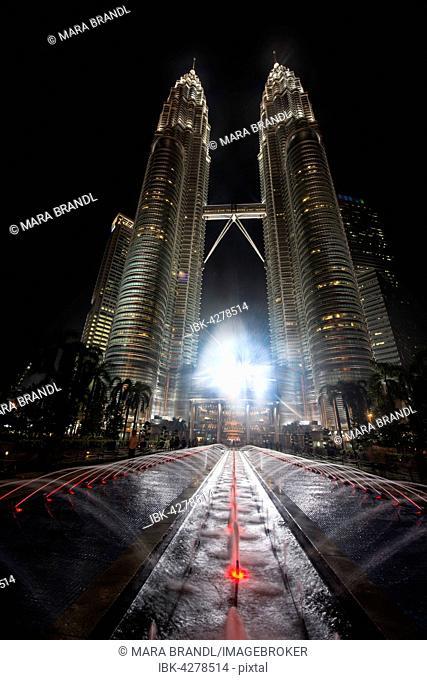 Fountain in front of illuminated Petronas Towers at night, Kuala Lumpur, Malaysia
