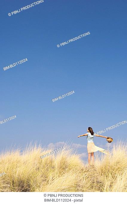 Caucasian woman standing in tall grass