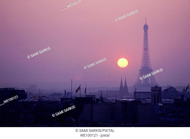 Silhouette of the Eiffel Tower surrounded by rooftops at sunset, Paris, France