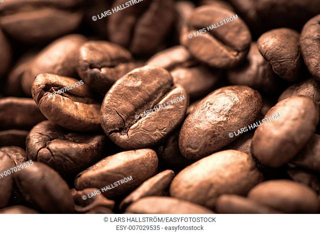 Closeup of dark roasted coffee beans. Food and drink backdrop showing aromatic and beautiful coffee beans. Can be used as a conceptual image for breakfast time