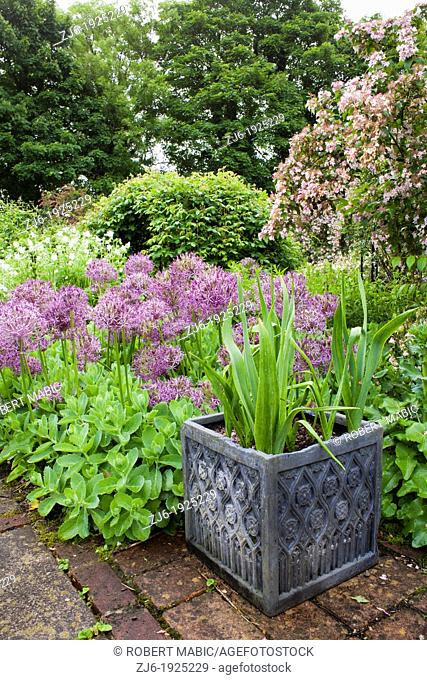 Decorative container with planting surrounded with spring borders of perennials and bulbs, Traditional romantic garden in Kent England