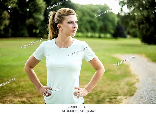 Sportive young woman standing in a park looking sideways
