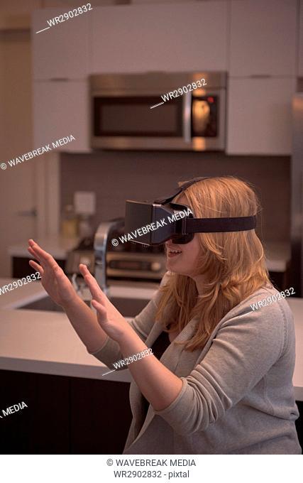 Woman gesturing while enjoying virtual reality simulator in kitchen