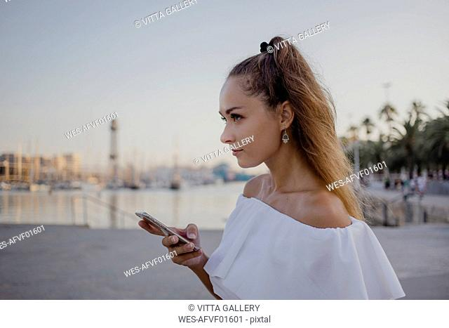 Young woman using smartphone at the harbour of Barcelona, portrait