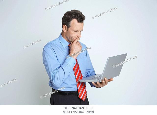 Studio shot of businessman with laptop