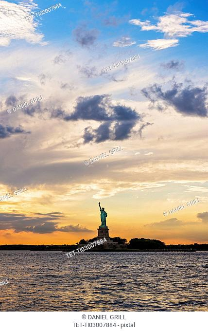 Silhouette of Statue of Liberty at sunset