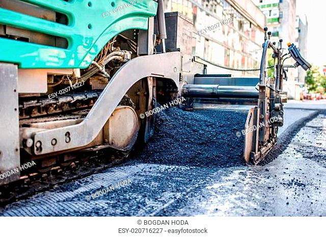 industrial truck laying fresh bitumen and asphalt at road construction site