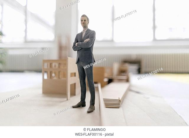 Miniature businessman figurine standing at architectural model