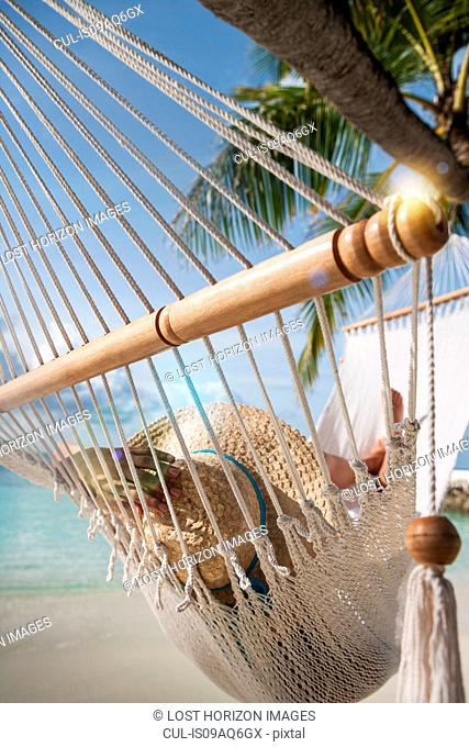 Young woman relaxing on a hammock on a tropical island