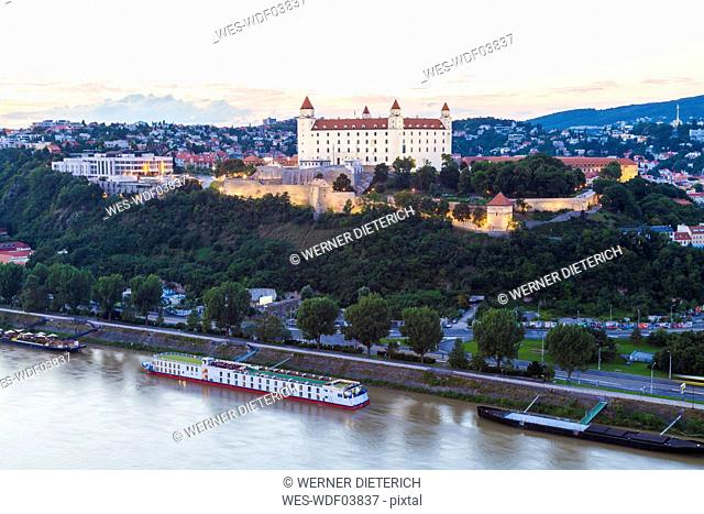 Slovakia, Bratislava, view to castle with river cruise ship on the Danube in the foreground at twilight