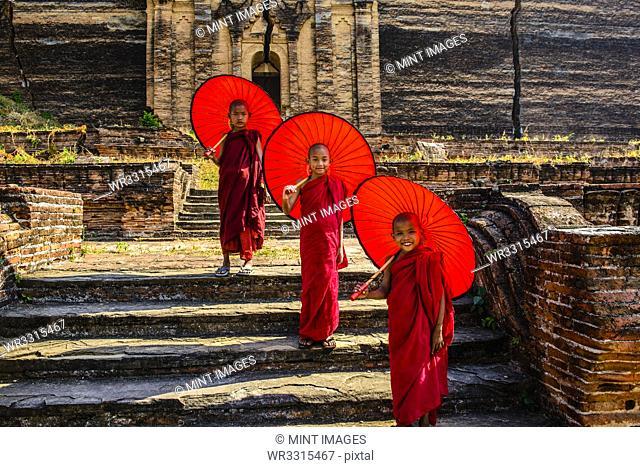 Asian monks standing under umbrellas near historic temple, Mingun, Mandala, Myanmar