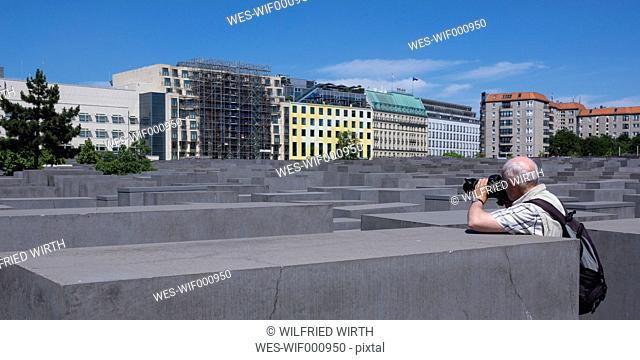 Germany, Berlin, Holocaust Memorial, Senior man photographing steles