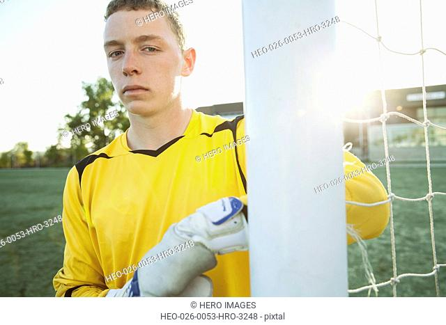 Soccer goalie with serious look by net
