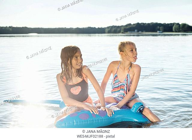 Two girls sitting on swim toy in the water