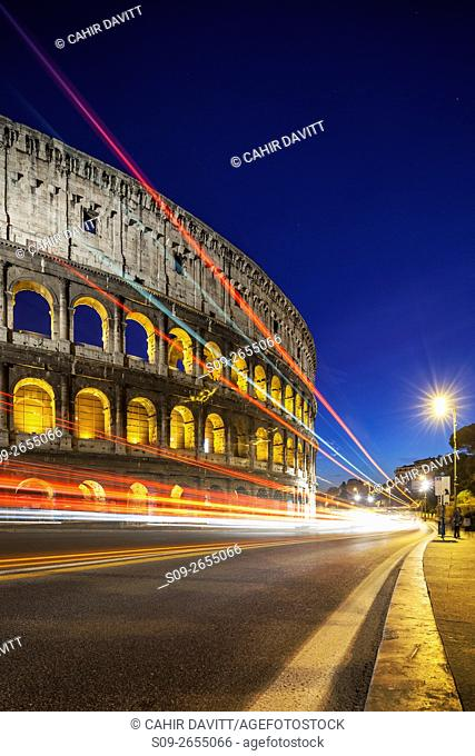 Side view of the Colloseum, viewed from the Piazza del Colosseo at twilight, with vehicular light trails, Campitelli, Rome, Lazio, Italy
