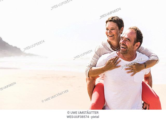 Happy mature man carrying wife piggyback on the beach