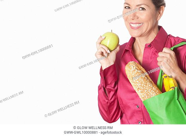 Woman holding a shopping bag of groceries with fruits