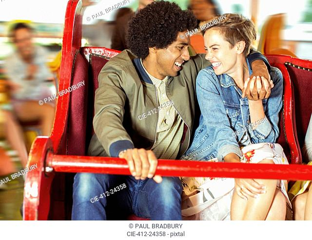 Cheerful couple on carousel in amusement park