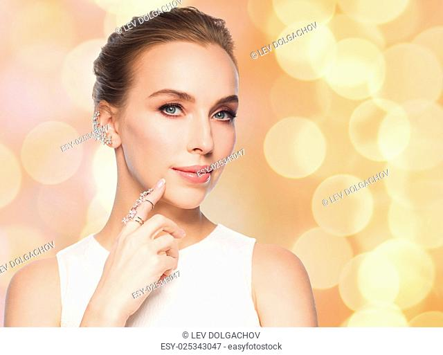 jewelry, luxury, wedding and people concept - smiling woman in white dress with diamond earring and ring over beige holidays lights background