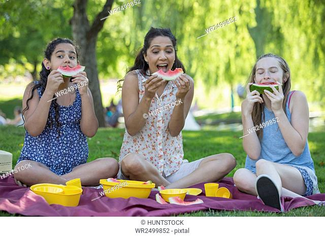 Happy Hispanic family having a picnic and eating watermelon in a park