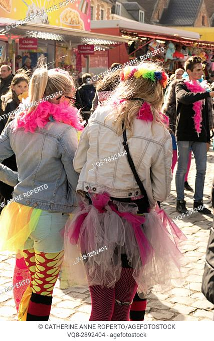 Young girls dressed in bright tights, feathers and net at the fairground stalls celebrating the Parade of the Giants in the Easter carnival at Cassel, France