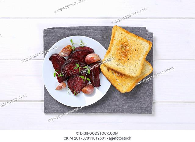plate of baked beetroot and garlic with toasted bread on grey place mat