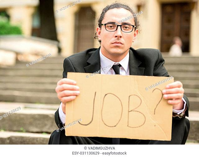 Man in suit sitting at stairs with sign in hands. Unemployed man looking for job