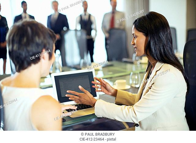 Businesswomen sitting with tablet pc in conference room