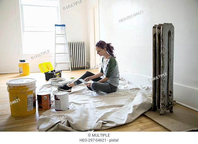 Woman viewing paint swatches on drop cloth in living room
