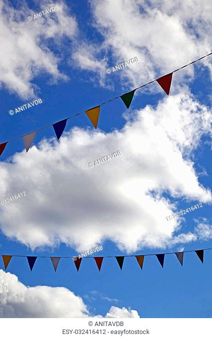 Colourful bunting flying in the wind on a sunny day with a blue sky and white clouds. With space for text