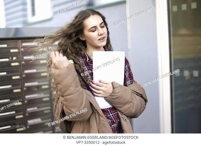 emotive woman holding letter in front of postbox at home, apartment building