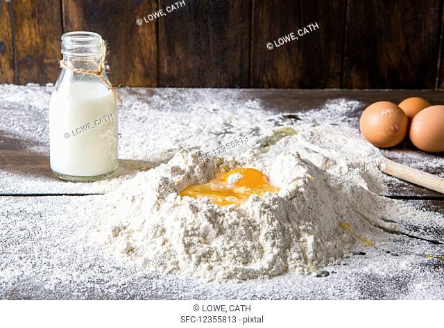 Flour milk and broken eggs on dark board