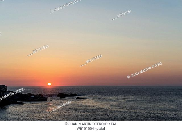 The sun falls on the sea from a reddish sky, seen from an island in the Pacific Ocean